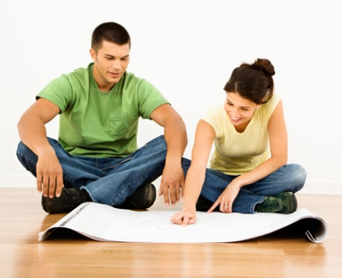 Attractive young adult couple looking at house plans.