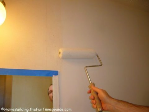 blue painters tape and rolling primer on drywall