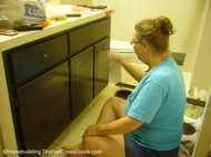 here's Sandy busy refinishing bathroom cabinets in our home