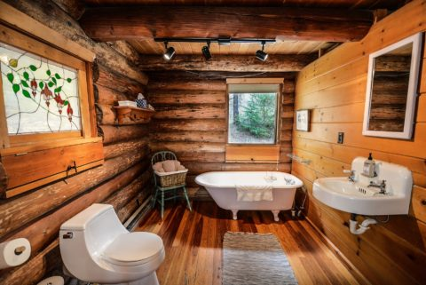 A rustic log cabin bathroom that includes the most important fixtures: toilet, bathtub, and sink.